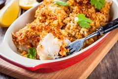 Baked cod fish in breadcrumbs in gratin dish closeup stock photos