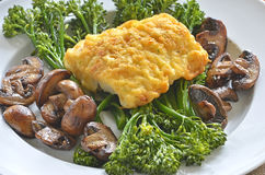 Baked cod with vegetables. Cheddar and potato crusted baked cod with steamed broccolini and sauteed crimini mushrooms Royalty Free Stock Photos