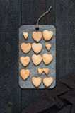 Baked cookies-hearts on the wooden table. Baked cookies-hearts on the vintage wooden table Royalty Free Stock Image