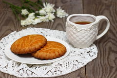 Baked cookies with tea. And flowers. Shallow DOF royalty free stock images