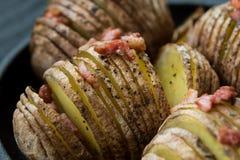 Baked cortou a batata com bacon e especiarias Fotografia de Stock Royalty Free
