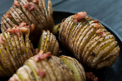 Baked cortou a batata com bacon e especiarias Imagem de Stock Royalty Free
