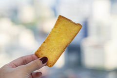 Baked crispy butter bread. A piece of baked crispy butter bread in human hand Royalty Free Stock Photos