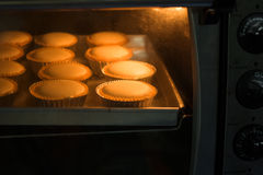 Baked cup cakes on a tray in the oven Stock Photo