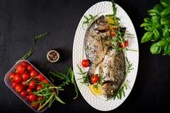 Baked dorado fish in garlic dill sauce and lemon. Royalty Free Stock Images