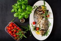 Baked dorado fish in garlic dill sauce and lemon Royalty Free Stock Photography