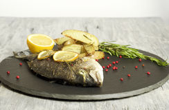 Baked dorado with rosemary baked potato wedges. Food & Dishes for Restaurants, Cuisine of the peoples of the world, Healthy Recipes Royalty Free Stock Photography