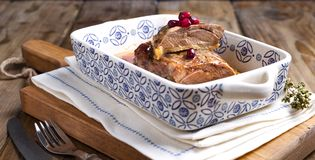 Baked duck fillet with pomegranate berries in a ceramic baking tray with patterns on a wooden table. Food for healthy nutrition. Free space for tex royalty free stock photos