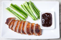 Baked duck with hoisin sauce, cucumbers and shallots. Selective focus, close-up royalty free stock photography