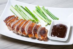 Baked duck with hoisin sauce, cucumbers and shallots. Selective focus, close-up royalty free stock image
