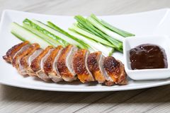 Baked duck with hoisin sauce, cucumbers and shallots. Selective focus, close-up stock image