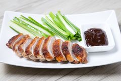 Baked duck with hoisin sauce, cucumbers and shallots. Selective focus, close-up stock photo