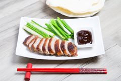Baked duck with hoisin sauce, pancakes, cucumbers and shallots. Selective focus, close-up stock images