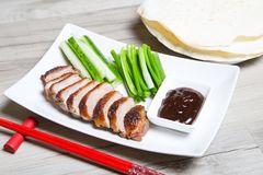 Baked duck with hoisin sauce, pancakes, cucumbers and shallots. Selective focus, close-up stock photo