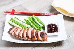 Baked duck with hoisin sauce, pancakes, cucumbers and shallots. Selective focus, close-up royalty free stock image