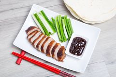 Baked duck with hoisin sauce, pancakes, cucumbers and shallots. Selective focus, close-up royalty free stock photography