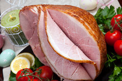 Baked Easter Ham with Vegetables. Baked honey ham with fresh tomatoes, parsley, and lemon. Ester eggs decoration, candles, and champagne Royalty Free Stock Photo