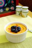 Baked egg custard, blue berries, jam. A photograph showing a sweet dessert dish of chiled baked vanilla egg custard in a white ramekin, topped with a sprinkling Royalty Free Stock Image