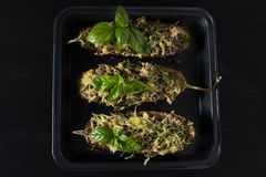 Baked eggplant with basil and cheese. In dark background Stock Photography
