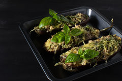 Baked eggplant with basil and cheese. In dark background Stock Images