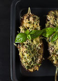 Baked eggplant with basil and cheese. In dark background Royalty Free Stock Image