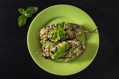 Baked eggplant with basil and cheese. In dark background Stock Photos