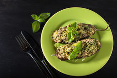 Baked eggplant with basil and cheese. In dark background Royalty Free Stock Photography