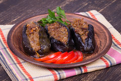 Baked eggplant stuffed with onions, cherry plums and walnuts. On the plate, close up Stock Images
