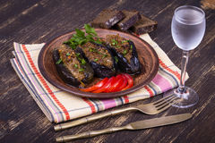 Baked eggplant stuffed with onions, cherry plums and walnuts. On the plate, close up Royalty Free Stock Image
