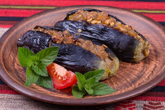 Baked eggplant stuffed with onions, cherry plums and walnuts. On the plate, close up Stock Photo