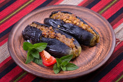 Baked eggplant stuffed with onions, cherry plums and walnuts. On the plate, close up Royalty Free Stock Photography