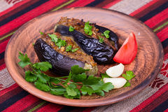 Baked eggplant stuffed with onions, cherry plums and walnuts. On the plate, close up Royalty Free Stock Photos