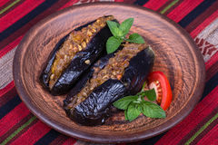 Baked eggplant stuffed with onions, cherry plums and walnuts. On the plate, close up Royalty Free Stock Photo