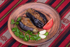 Baked eggplant stuffed with onions, cherry plums and walnuts. On the plate, close up Stock Photography