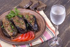 Baked eggplant stuffed with onions, cherry plums, walnuts on the plate and a glass of cold vodka. Close up Stock Images