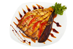 Baked eggplant with tomatoes and cheese on plate on white backgr Stock Photography