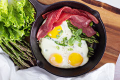 Baked eggs with asparagus and bacon Stock Photography