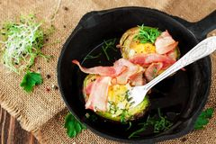 Baked eggs in avocado with bacon stock images
