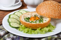 Baked eggs in a bun with vegetables on a white plate Royalty Free Stock Images