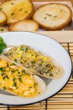 Baked eggs, butter and shellfish with chopped bread royalty free stock image