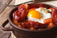 Baked eggs with chorizo and vegetables in the pot. Horizontal Royalty Free Stock Image