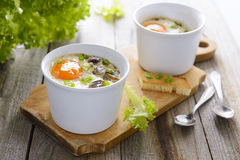 Baked eggs with mushrooms, cream and chives Stock Photo