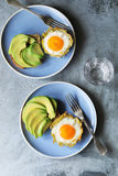 Baked eggs in potato nests with avocado toast. Top view Royalty Free Stock Photography