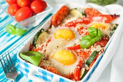 Baked eggs with vegetables stock photography
