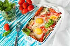Baked eggs with vegetables stock images