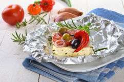 Baked feta. Greek feta baked in foil with herbs, vegetables and olive oil Royalty Free Stock Photo