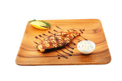 Baked fish. With a lemon on a wooden dish on a white background royalty free stock photo
