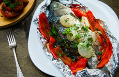 Baked fish with bell peppers, onions and herbs Stock Photos