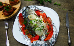 Baked fish with bell peppers, onions and herbs Royalty Free Stock Image