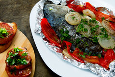 Baked fish with bell peppers, onions and herbs Royalty Free Stock Photo